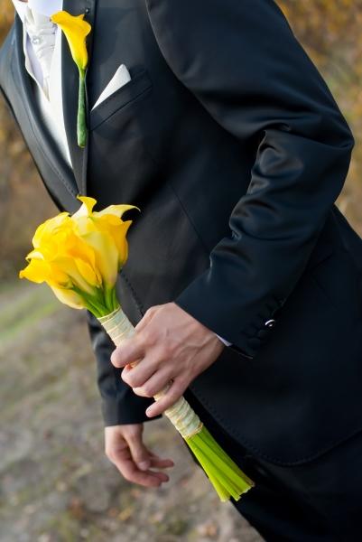 Pan młody z żółtym bukietem ślubnym